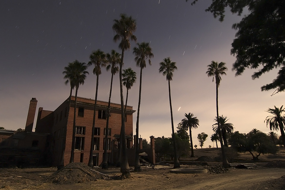 Overview  :::::  Sad and forgotten, this once stately hotel vainly tries to hide from vandals behind its screen of swaying palms